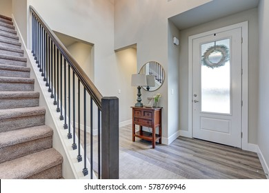 Grey foyer with laminate flooring, high ceiling, furnished with console table next to white front door and staircase with metal and wood railings. Northwest, USA.