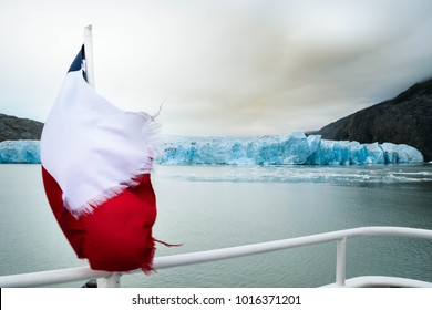 Grey glacier from ferry at Torres del Paine National park, Chilean flag. Patagonia, Chile