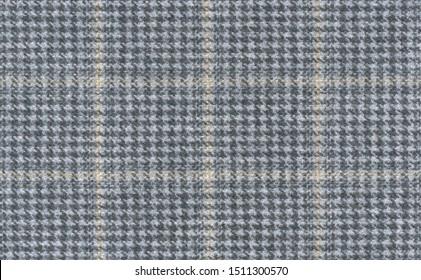 Grey Glenurquhart check is made of woolen fabric. Herringbone tweed, Wool Background Texture. Coat close-up. Expensive men's suit