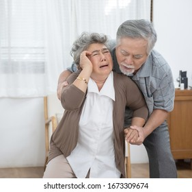 Grey haired asian old husband helping overcome problem, supporting unhappy mature wife at home, sitting on couch, Elder senior woman suffering from headache, having health problem.