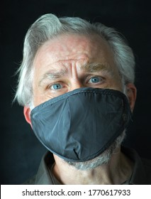 Grey haired man with beard wearing a face mask