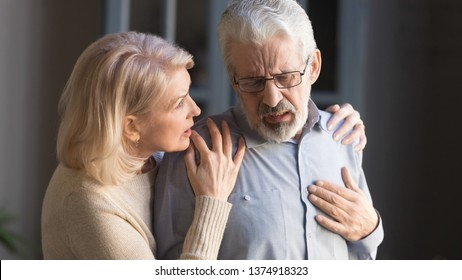 Grey haired man touching chest, having heart attack, feeling pain, suffering from heartache disease at home, mature woman supporting, embracing him, middle aged family, horizontal banner, close up