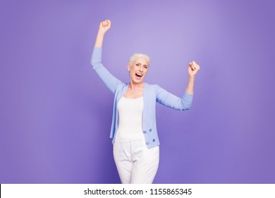 Grey haired old happy woman wearing casual, raising hands up, celebrating party winning, opened mouth. Isolated over violet purple background