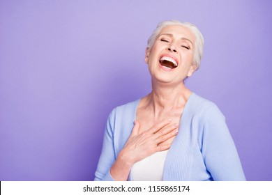 Grey haired old nice beautiful laughing woman, closed eyes, copy blank empty space. Isolated over violet purple background