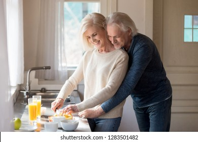 Grey haired retirees husband and wife standing in kitchen at home preparing healthy vitamin breakfast, female cutting fruit using knife, male standing behind her couple enjoy time together on weekend