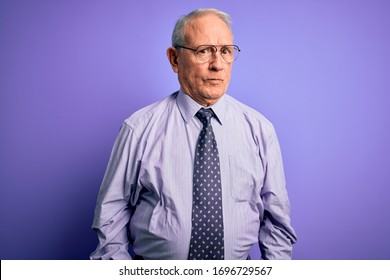 Grey haired senior business man wearing glasses standing over purple isolated background skeptic and nervous, frowning upset because of problem. Negative person.