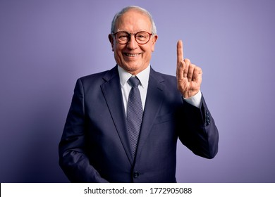 Grey haired senior business man wearing glasses and elegant suit and tie over purple background showing and pointing up with finger number one while smiling confident and happy.