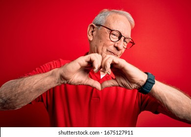 Grey haired senior man wearing glasses and casual t-shirt over red background smiling in love doing heart symbol shape with hands. Romantic concept.