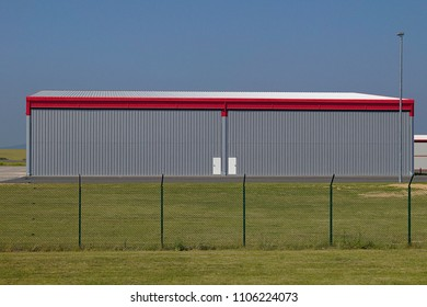 Grey hangar with red and two white doors at the airport