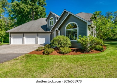Grey house with long driveway lush green grass large yard and sunny woodendeck