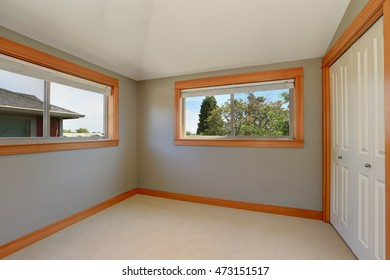 Grey interior of empty room with two windows and white doors closet. Northwest, USA