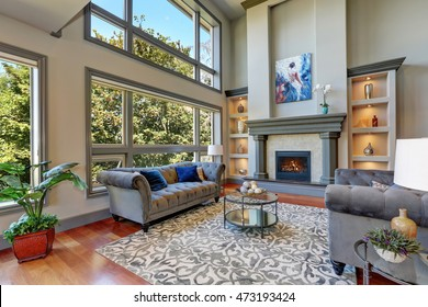 Grey interior of high vaulted ceiling family room in luxury house with fireplace and large windows. Northwest, USA.