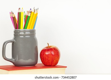 grey jar of colouring pencils and a ripe red apple standing on a red textbook against a white background