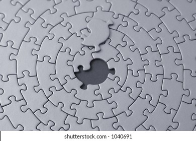 grey jigsaw with the missing piece laying above the space - shallow DOF, focus is on the hole