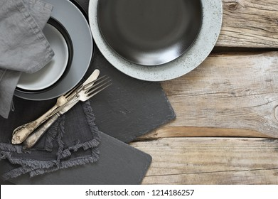 Grey kitchen utensils on rough distressed wooden table: crockery, silverware, slate trays and linen towels. Top view point.