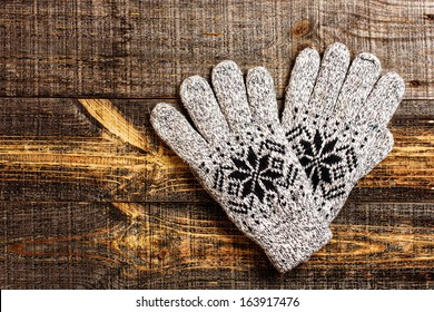 Grey knitted winter gloves isolated on wooden boards