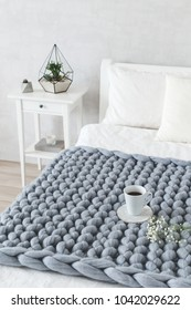 Grey knitted woolen merino chunky blanket. Thick yarn. Stylish cozy scandinavian bedroom interior: bed with white linen, bedside table, grey stucco or cement wall, cup of tea, gypsophila flowers.