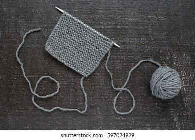 Grey knitting on black background