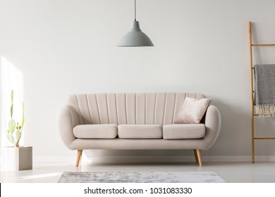 Grey lamp hanging above a couch with silver pillow in white living room interior
