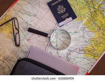 grey laptop in case sitting on wooden table next to map, stylish glasses, passport and magnifying class. This picture is ideal for any freelancer writer, author or digital nomad who travels the world