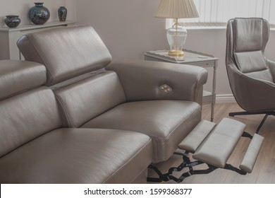 Grey Leather sofa recliner in open position in living room, with side table and single chair.