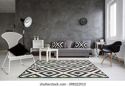 Grey living room with sofa, chairs, standing lamp, pattern carpet and trendy decorative details