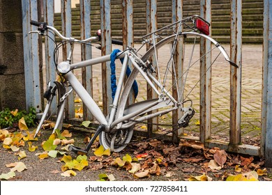 grey locked bike with stolen wheels