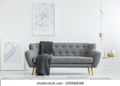 Grey lounge with dark blanket standing in white living room interior with two map posters, gold bulb lamp and books on a small table