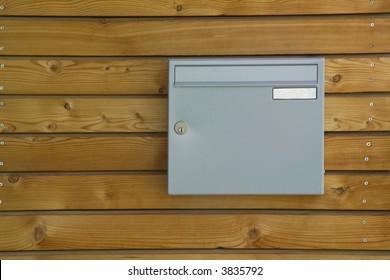 a grey mailbox on a brown housewall