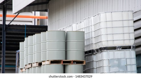 grey metal chemical steel tank and white ibc container in outdoor stock yard of factory.