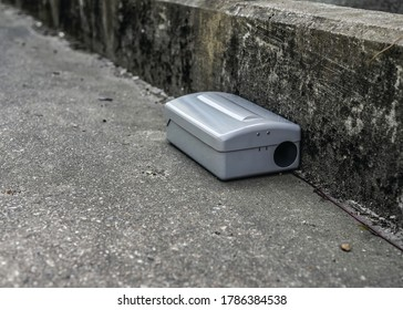 Grey Metal external rodent rat bait station outside against a wall close up.  Pest Control.