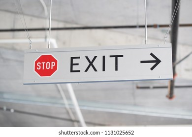 Grey metallic stop and exit sign with arrow.