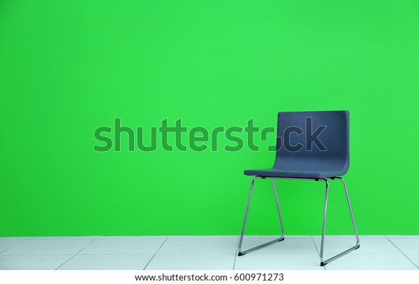 Grey modern chair on green wall background