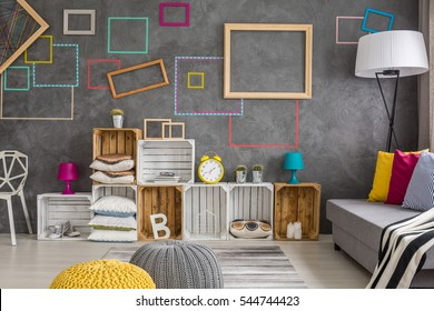 Grey modern living room with wooden boxes shelf full of colorful decorations