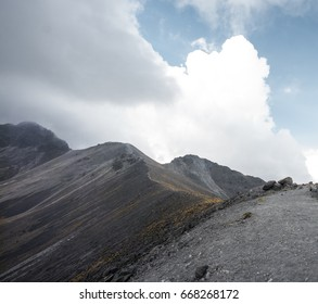 grey mountain top with yellow details and big clouds