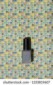 Grey nail lacquer on trendy graphic patterned colorful background. Beauty and fashion conception.