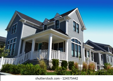 Grey New England Style Suburban Dream Home with Large Front Porch