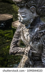 Grey and old traditional balinese statue with detailed ornaments covered by white spider web on a sunny day in Tirta Gangga garden. Stepping stones cross the green and clear water in the background.