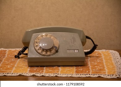 A grey old vintage rotary telephone with a rotary dial, on a vintage 1970s tablecloth, and with drab wallpaper.