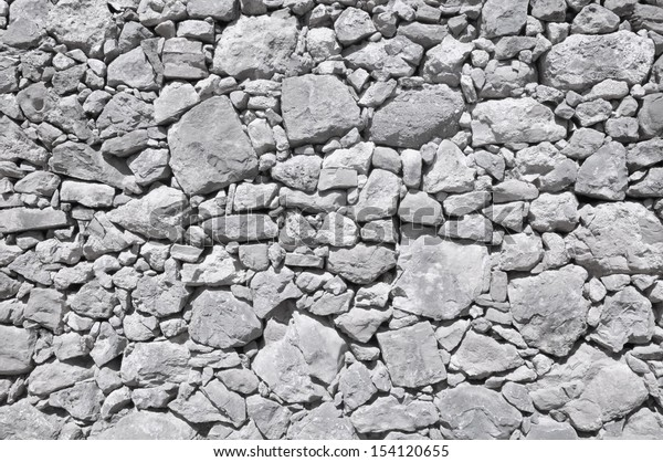 grey old wall made of big and little rough stones without cement