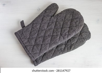 Grey Oven Mitts On White Wood Background