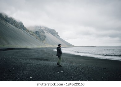 Grey palette image of sandy volcanic beach on cloudy and gloomy day, impressive epic mountains in distance, young man in jacket walks alone towards water, concept lonely or adventure in iceland