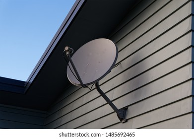 A grey parabolic dish on the side of a weatherboard house