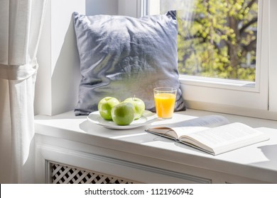 Grey pillow, book, apples and orange juice on window sill in bright interior. Real photo