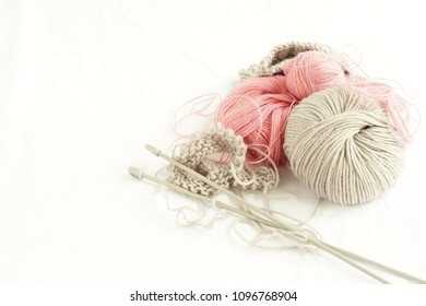 Grey and pink  knitting wool and knitting needles on white background. top view.copy space.Close up