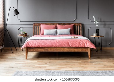 Grey and pink pillows on wooden bed in minimal bedroom interior with black lamp and molding on the wall