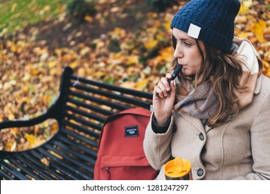 Grey and Pink Vape Pen held by Woman In Lifestyle Autumnal Setting