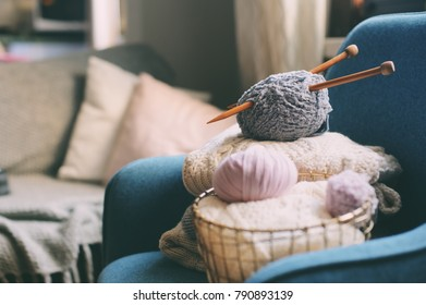Grey and pink Yarn ball with knitting needles in metallic basket with knitted sweaters on background. Hobby, cozy homely weekend and hugge concept.