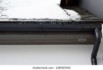 Grey plastic rain gutter with drain downspout pipe installed on asphalt shingles roof, wooden eaves with round ventilation grille and roof covered with snow and icicles in winter day.