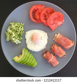 Grey plate with breakfast on the black background: egg, avocado, broccoli, tomato, hamon.